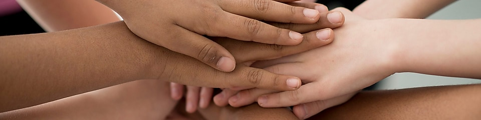 A multi-ethnic group of elementary age children are holding their hands together in huddle.