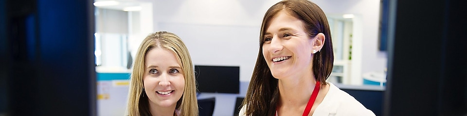 From right - Shell Graduate Samantha Palmer with her mentor Elise-Anne Muir standing in front of a computer screen