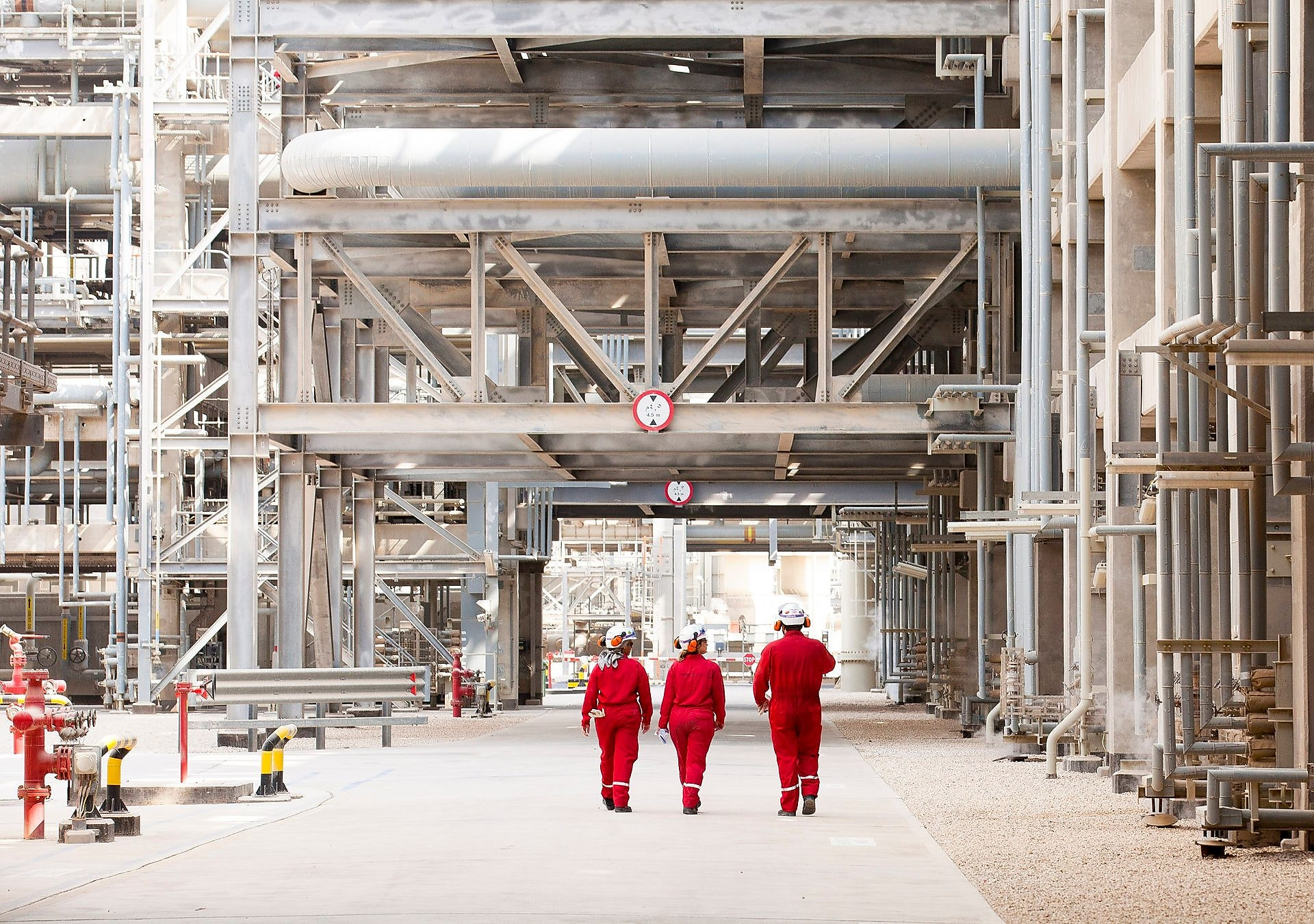 Three engineers walking through refinery grounds