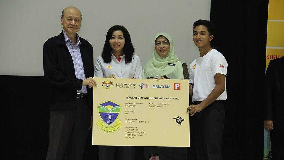 Tan Sri Datuk Sri Lee Lam Thye, Chairman of MIROS together with Pn Qamar Wan Noor, Senior Manager of Shell Downstream Business presenting MyLesen motorcycle license to Puan Zawiah binti Yahya, Principal of SMK Subang and Danial Amirul student rep Hakim b Mohd Zalizan