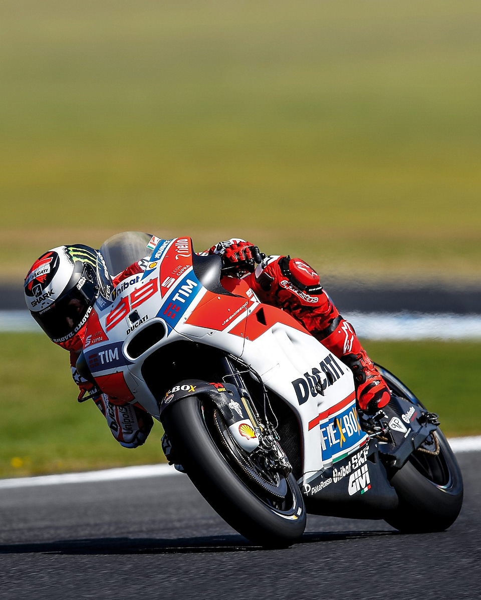 ducati superbike with rider cornering at speed on a racetrack