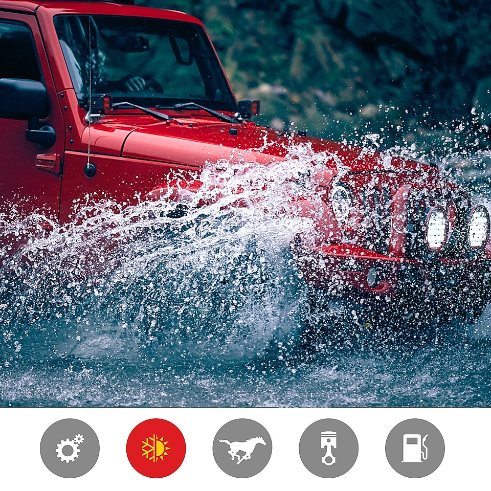 A red jeep splashes through a riverbed, indicating the extreme temperature performance product benefit
